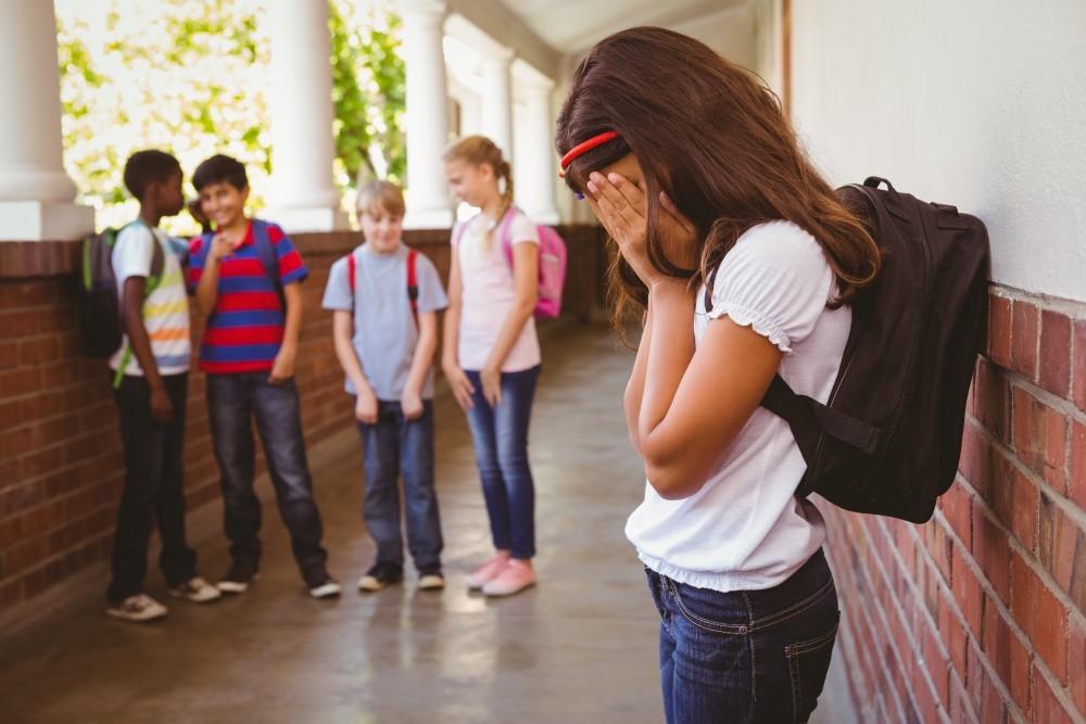 Sad schoolgirl with friends in background at school corridor
