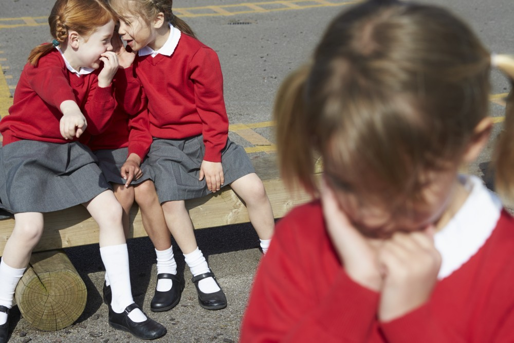 Female Elementary School Pupils Whispering In Playground