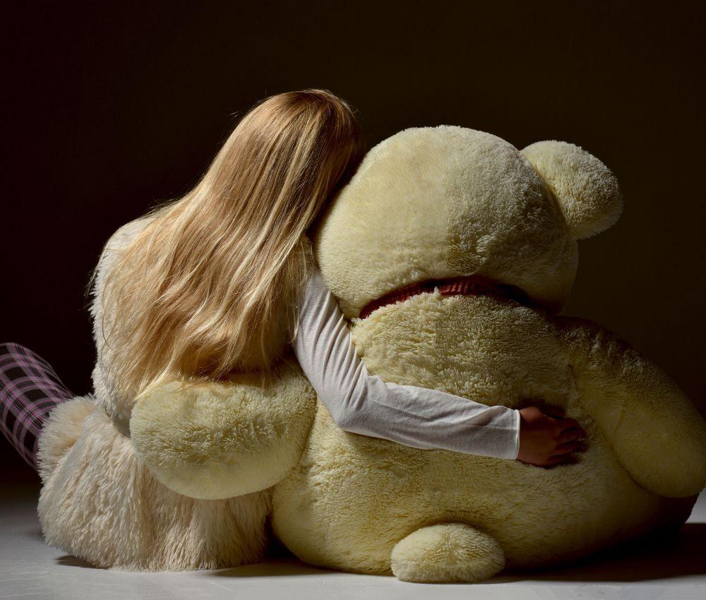 teenage girl sitting backward hugging big teddy bear back view