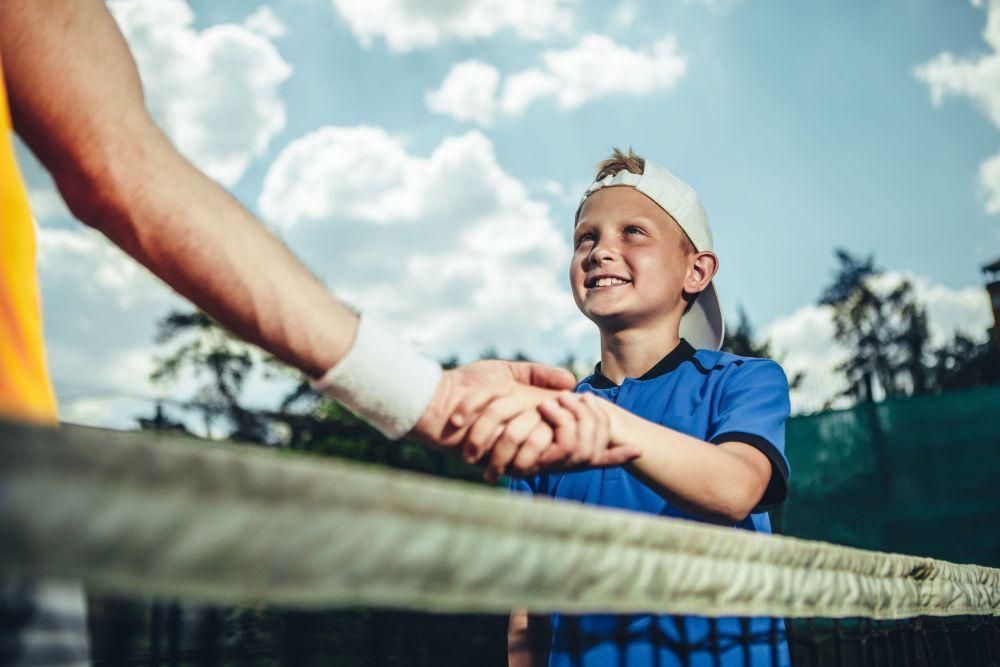 Optimistic child shaking hand of man
