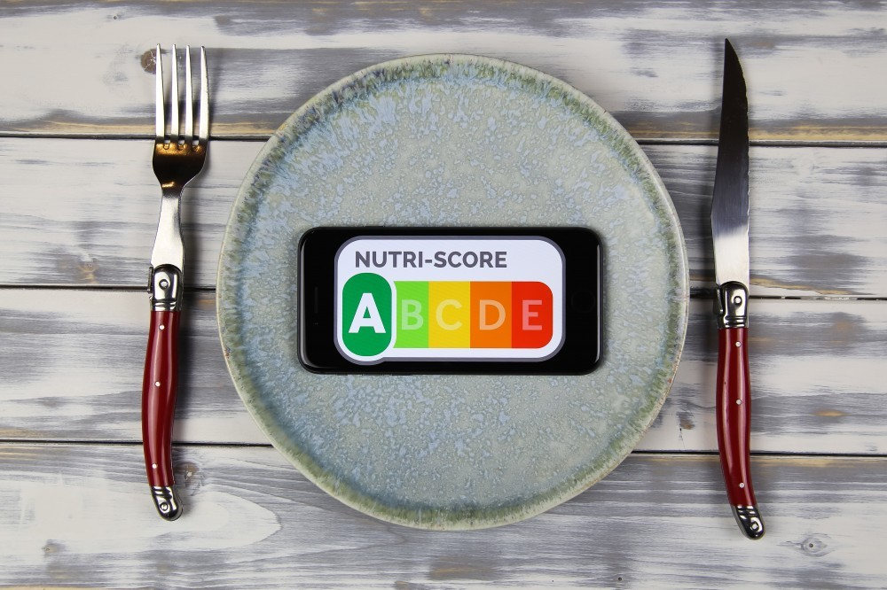 Viersen, Germany - February 9. 2021: Closeup of smartphone screen with logo lettering of nutri-score on plate with cutlery