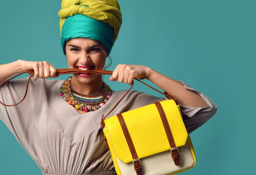 Woman yelling screaming and eating belt of hand hold stylish fashion yellow leather bag
