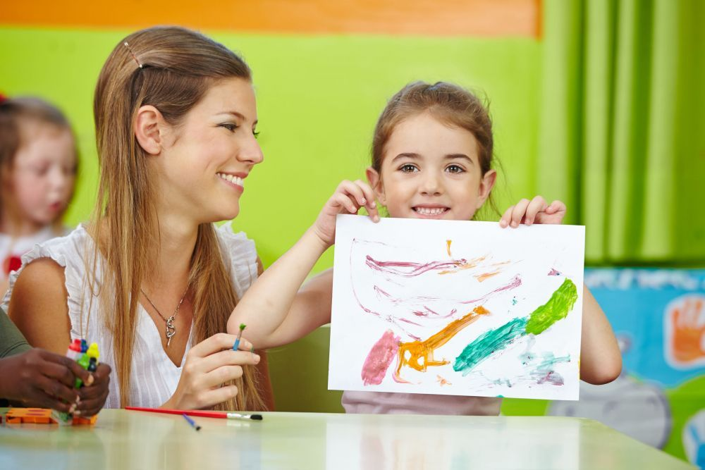 Girl showing self drawn painting in kindergarten