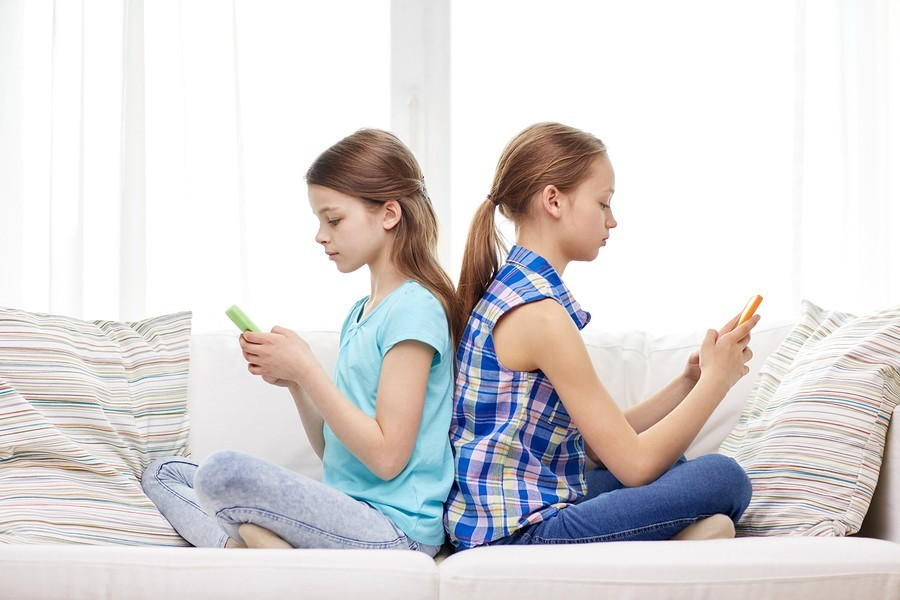 people, children, technology, friends and addiction concept - little girls with smartphones sitting
