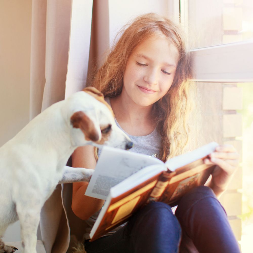 Girl reading book at home with dog