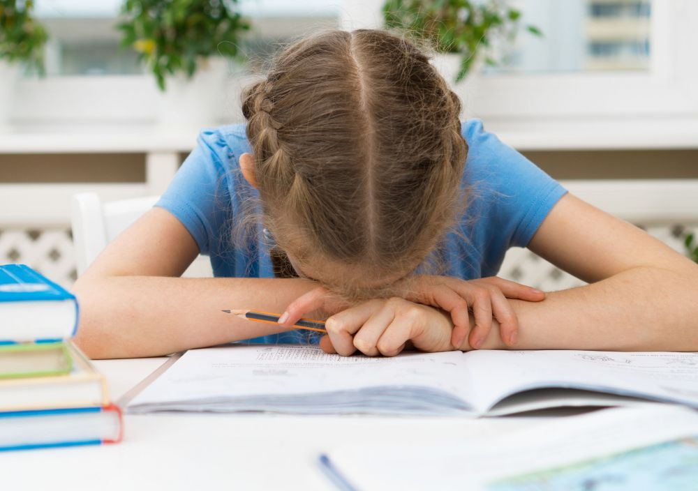 Little girl don\'t want to do her homework.